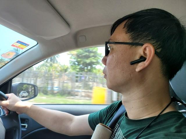 ผู้ชายผมสั้น ใส่แว่น สวมเสื้อยืดคอกลมสีเขียว กำลังขับรถยนต์อยู่ ในหูข้างซ้าย สวมหูฟัง Huawei FreeBuds 4i