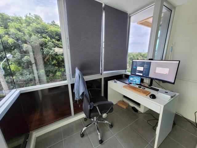 พื้นที่ระเบียงที่รีโนเวทให้เป็นห้องแล้ว มีการติดม่านบังแดด ฟิล์มกรองแสง และวางโต๊ะทำงาน มีโน้ตบุ๊ก มีคอมพิวเตอร์ และจอคอมพิวเตอร์วางอยู่