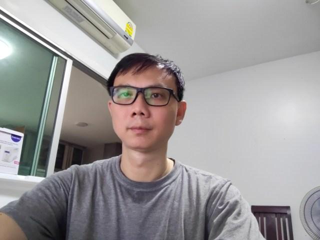 รูปของผู้ชายผมสั้น ใส่แว่น และเสื้อยืดสีเทา