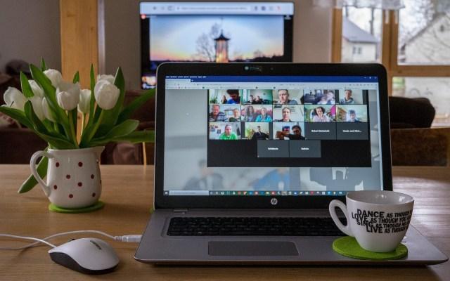 คอมพิวเตอร์ที่กำลังเปิดโปรแกรม Zoom ผ่านเว็บไซต์เพื่อประชุมออนไลน์ โดยมีแก้วกาแฟวางอยู่บนตัวเครื่อง