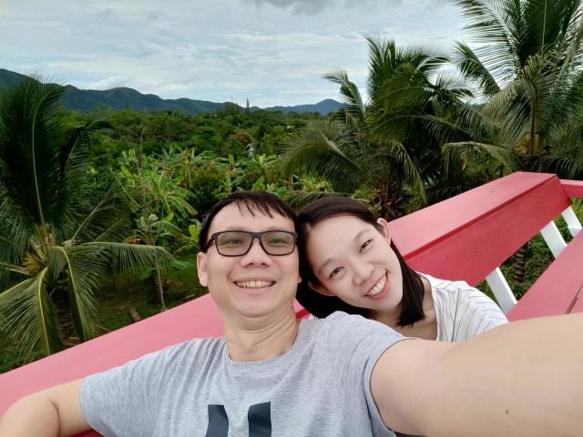 ผมและภรรยาถ่ายภาพเซลฟี่ริมระเบียงไม้ โดยมี