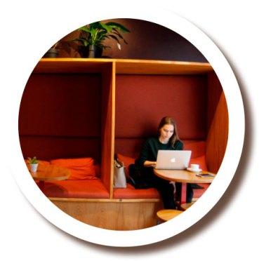 Bilde av ung kvinne som sitter med en PC på kaffebar