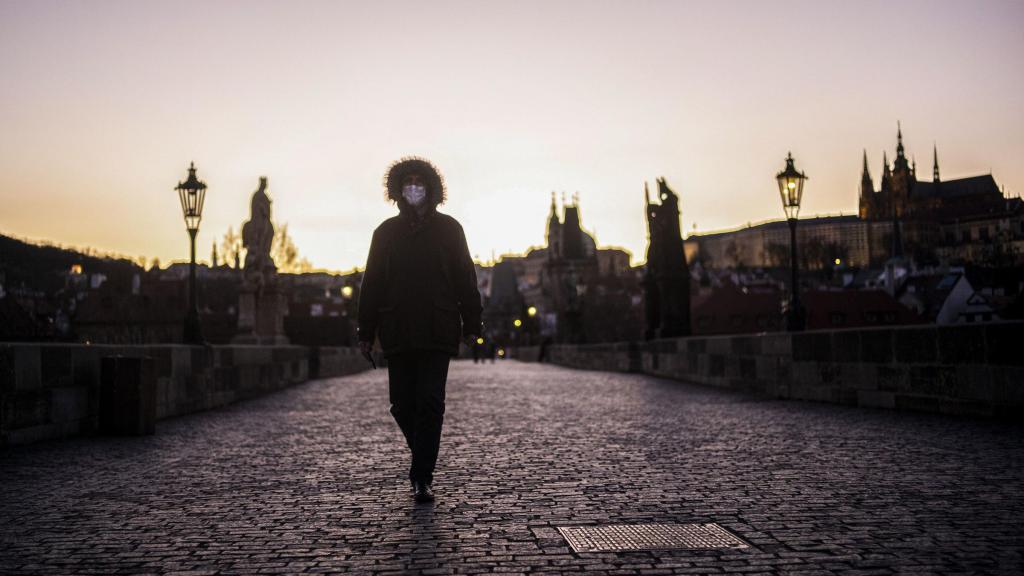 Man wearing a face-mask walking on the Charles Bridge in Prague