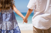 Children holding hands on the beach