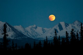 The blood moon rises over the mountains at Denali National Park & Preserve.