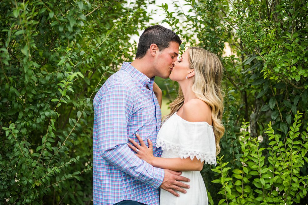 two people greenery romantic engagement kiss