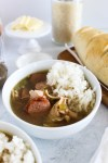Gumbo in a bowl with rice and French bread in the background.
