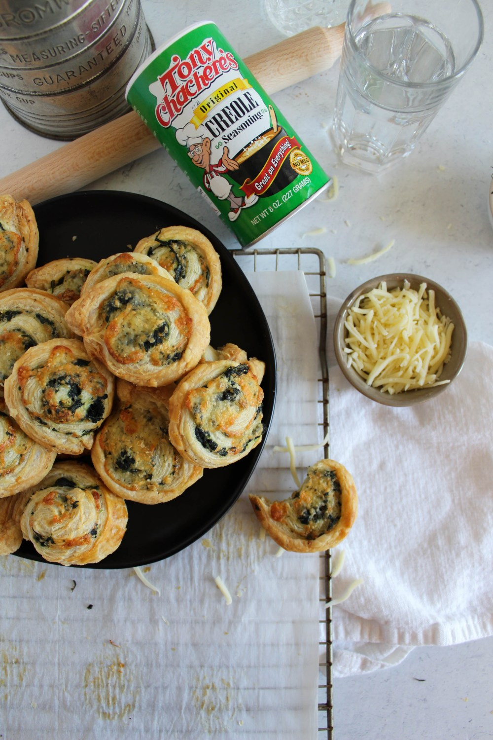 overhead view of spinach pinwheels on a plate with Tony's Chachere's seasoning in the background.