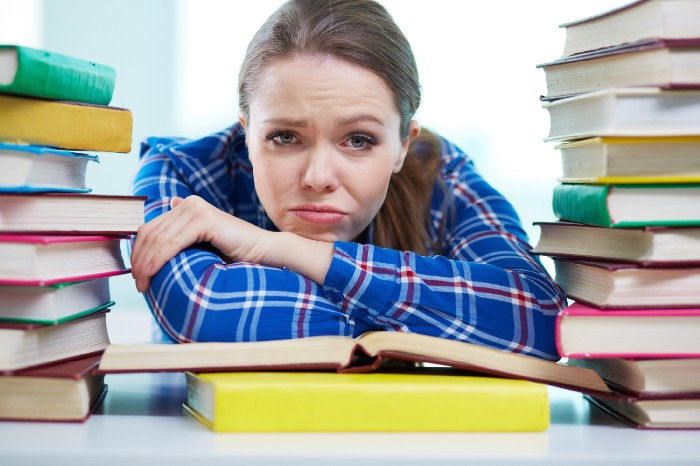 frustrated woman leaning on stack of books at the library
