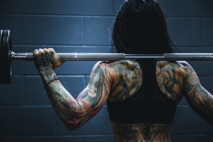 tattooed female cannabis athlete lifting weights at the gym