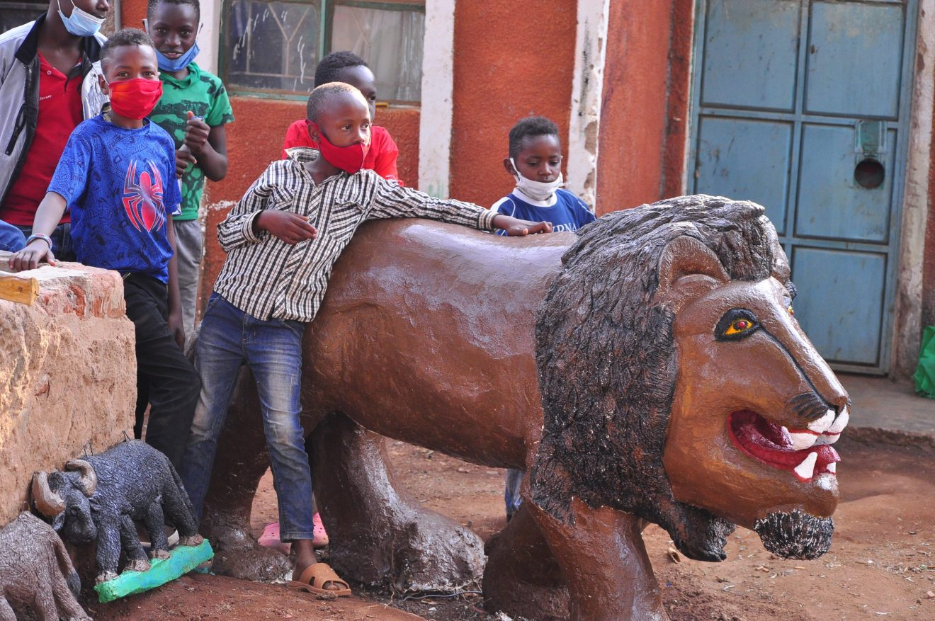 Children on August 10 who joined Matapato South Art Scupture group stand next to a sculture of a lion they made in their worshop