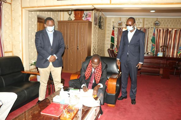 Governor Joseph ole Lenku assent water harvesting bill into law as nominated MCA Onesmus Ngogoyo and Daniel Kanchori -r- witness the event.