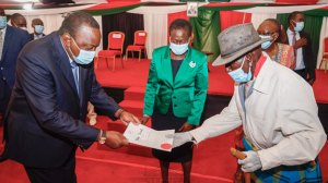 President Uhuru Kenyatta pictured handing over a title deed as Lands Cabinet Secretary Farida Karoney looks on during a ceremony on November 3, 2020.