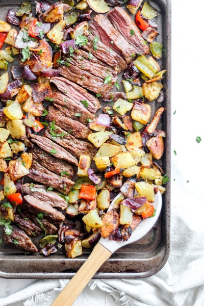 a baking sheet filled with roasted vegetables and a easy sheet pan bison steak