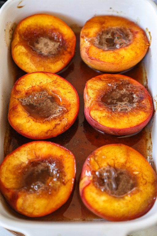Baked nectarine halves sitting in a bubbling sweet honey sauce in a white baking dish