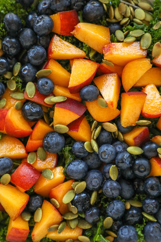 A light and refreshing summer salad made with peaches, blueberries, massaged kale and toasted pepitas all tossed in a lemon honey vinaigrette.
