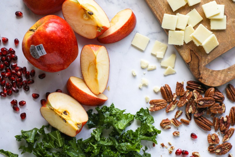 Crisp apples and juicy pomegranate arils, tender kale, white cheddar cheese and toasted pecans are all you need to make this delicious fall inspired salad! Plus it's made with a tangy maple-mustard dressing too!