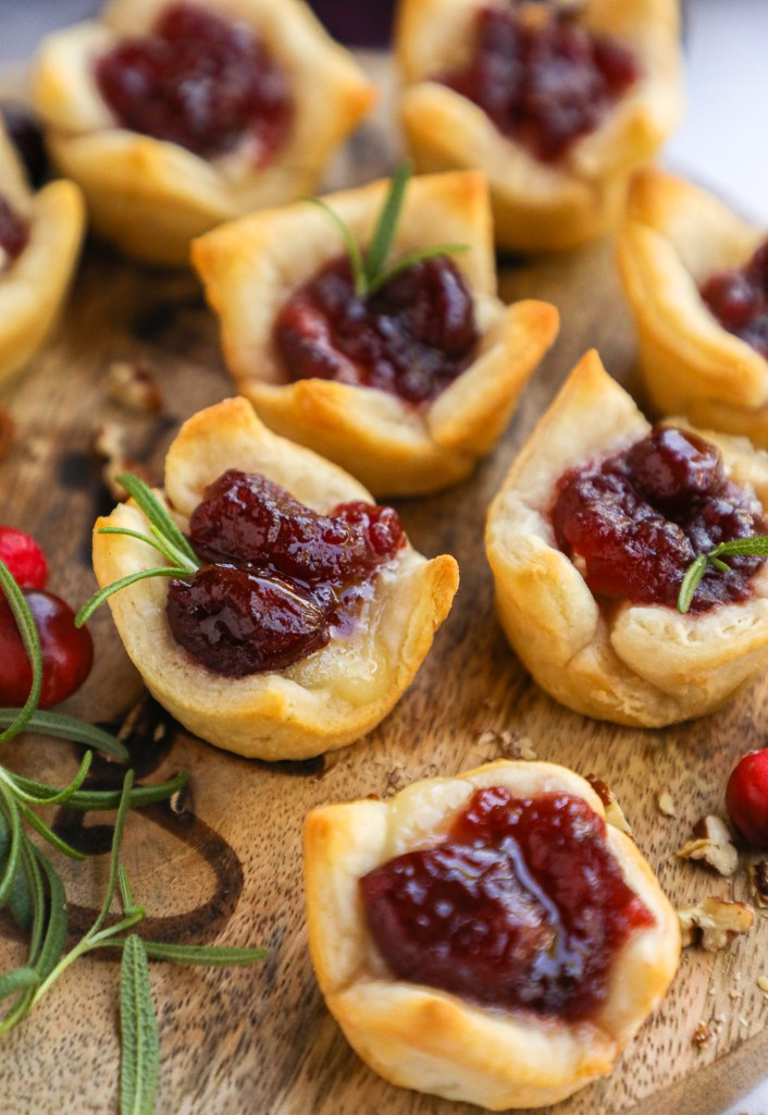 These mini brie bites are the perfect appetizer to serve at any party! They take just minutes to make and filled with gooey melted brie and tart cranberry sauce!