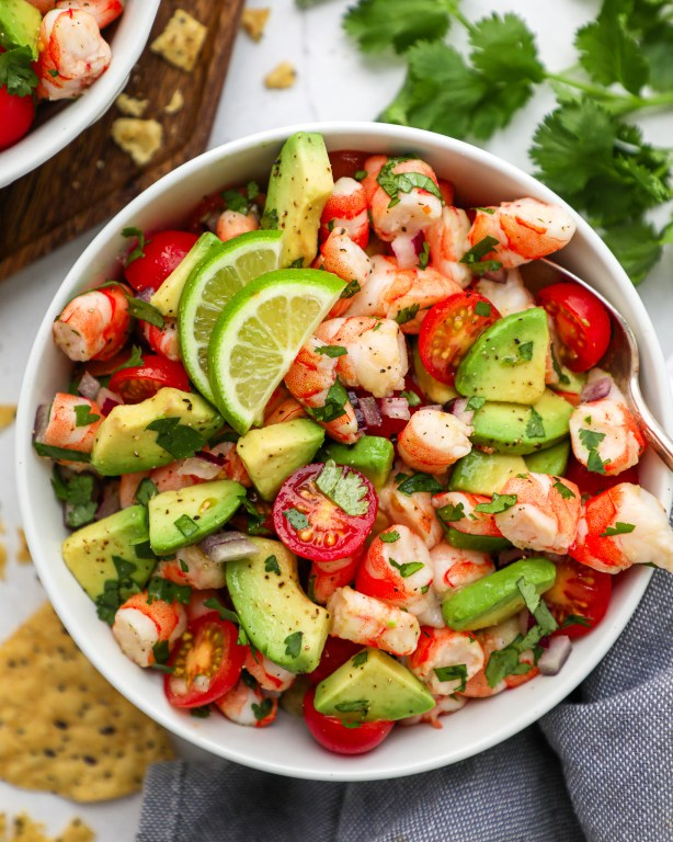 A salad made with precooked shrimp, avocado, tomato, red onion, cilantro lime juice in a white bowl and served with tortilla chips