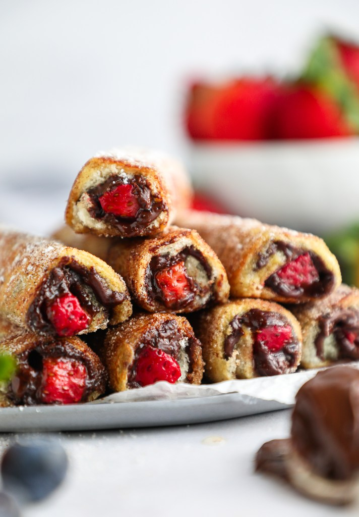 These delicious french toast roll ups are made with sliced strawberries and chocolate hazelnut spread all rolled up in white bread and coated with cinnamon sugar! They're such a fun treat for brunch!