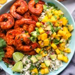 Easy chili lime shrimp bowls made with spicy Mexican shrimp, cilantro lime cauliflower rice and the best mango salsa! They're perfect for an easy lunch or dinner!