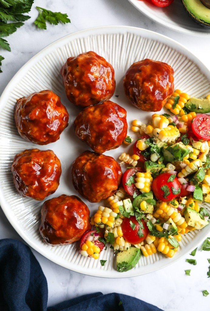 Close up of baked turkey meatballs covered in bbq sauce abd served with a fresh summer corn salad