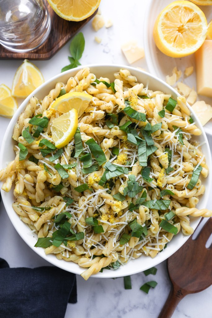 Lemon basil pasta salad in a white bowl surrounded by wooden serving utensils, parmesan cheese and lemon slices