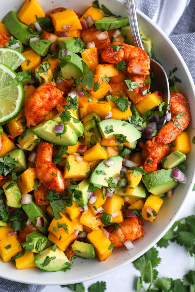 Close up photo of cut up seasoned shrimp, yellow mango, avocado, cilantro and onion in a speckled bowl with a wedge of lime on the side and a serving spoon sticking out
