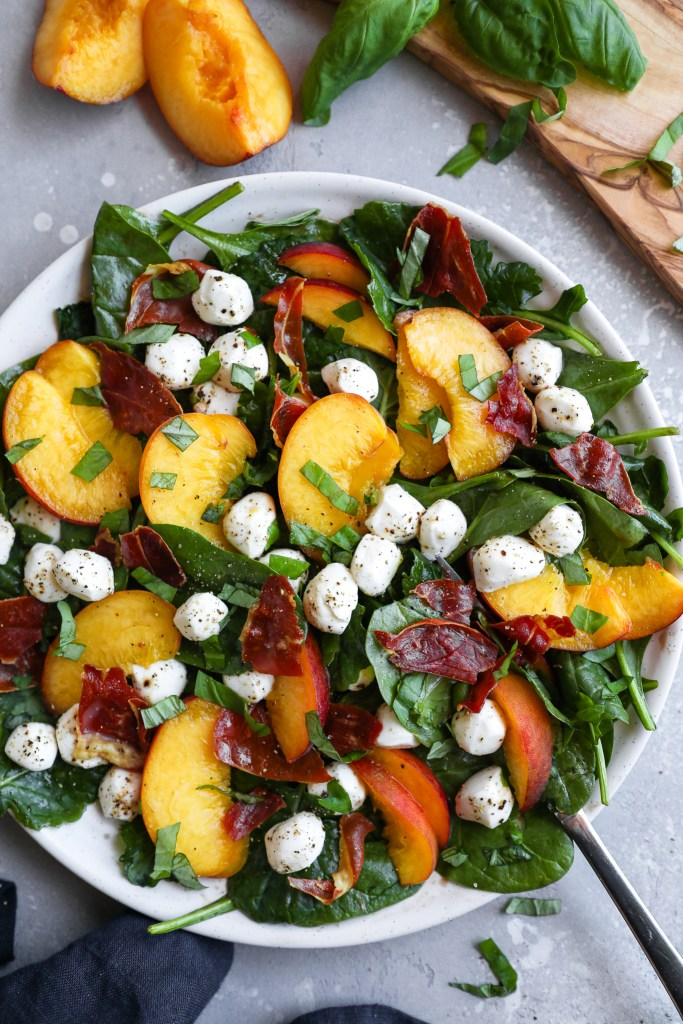 Peach caprese salad with prosciutto surrounded by fresh basil leaves and peach slices