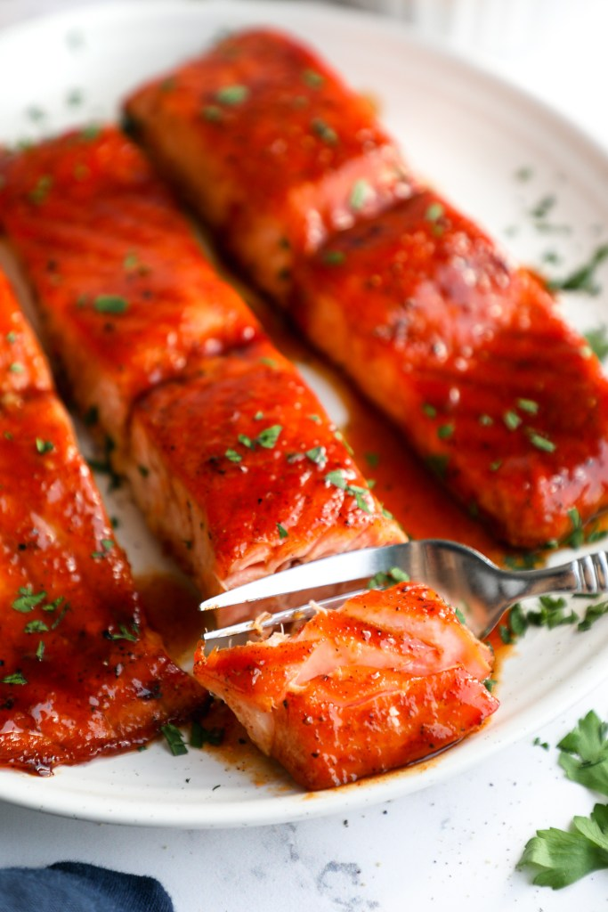 Close up photo of baked bbq salmon fillets on a white plate with a silver fork cutting into one of the fillets