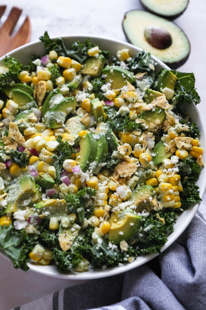 A summer kale salad made with fresh corn, red onion, cotija cheese, sliced avocado and tossed in a creamy cilantro lime dressing