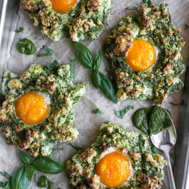 Pesto egg clouds on a baking sheet surrounded by sliced fresh basil and a spoonful of pesto