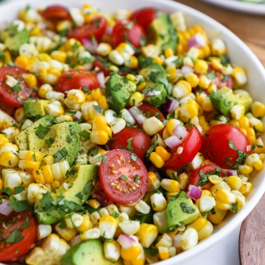 Closes up of fresh corn, tomato and avocado salad sitting in a white bowl on a marble counter top