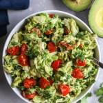Guacamole chicken salad in a white bowl with chopped grape tomatoes sprinkled on top
