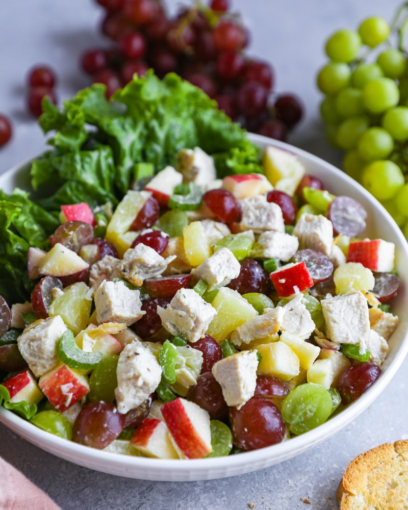 A bowl full of chicken fruit salad surrounded by red and green grapes and toasted garlic bread