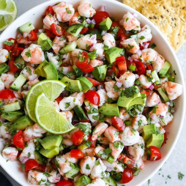 Easy shrimp ceviche in a large white bowl served with tortilla chips, avocado and lime wedges on the side