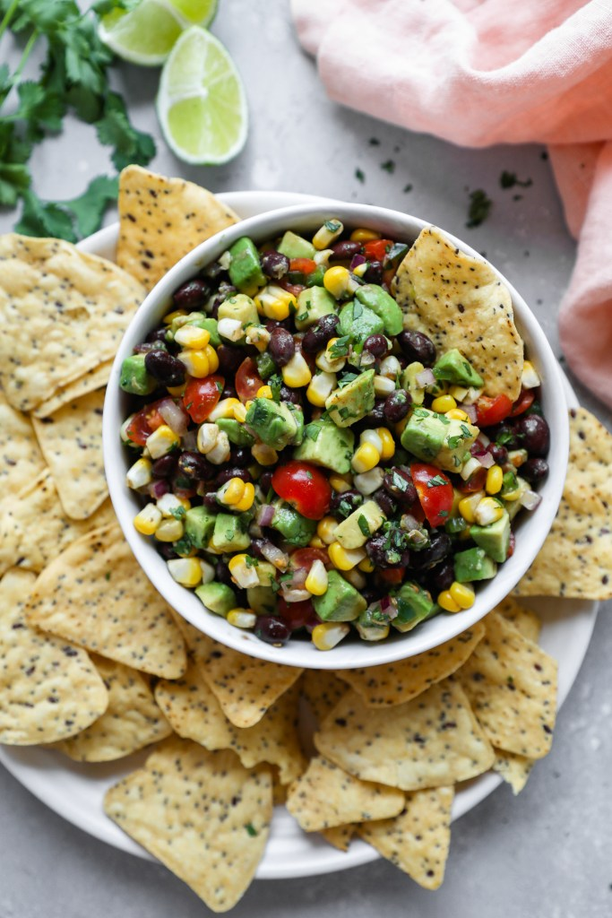Black bean salsa served in a white bowl with corn tortilla chips