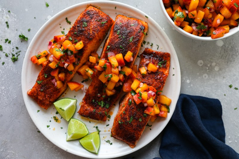 Baked sweet and spicy salmon sitting on a plate sprinkled with chopped cilantro and lime wedges on the side