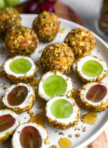 Goat cheese covered grape balls sitting on a white plate drizzled with honey