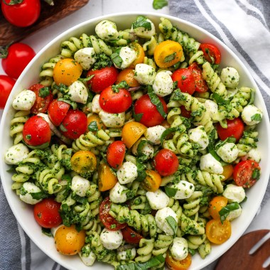 Pesto pasta salad sitting in a white bowl next to wooden sereving utensils and fresh cherry tomatoes