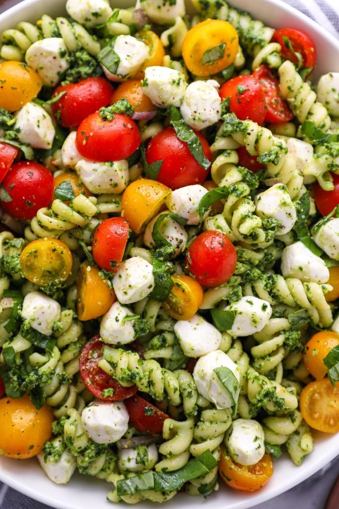 Close up photo of pasta salad made with mozzarella balls, tomatoes, red onion, basil and pesto