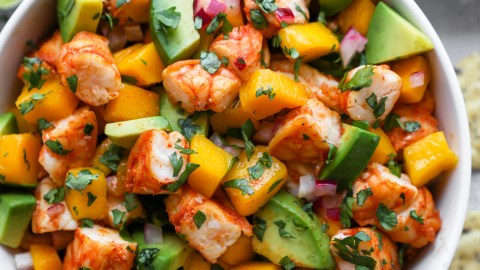 Spicy shrimp, mango and avoado salad in a small white bowl served with tortilla chips