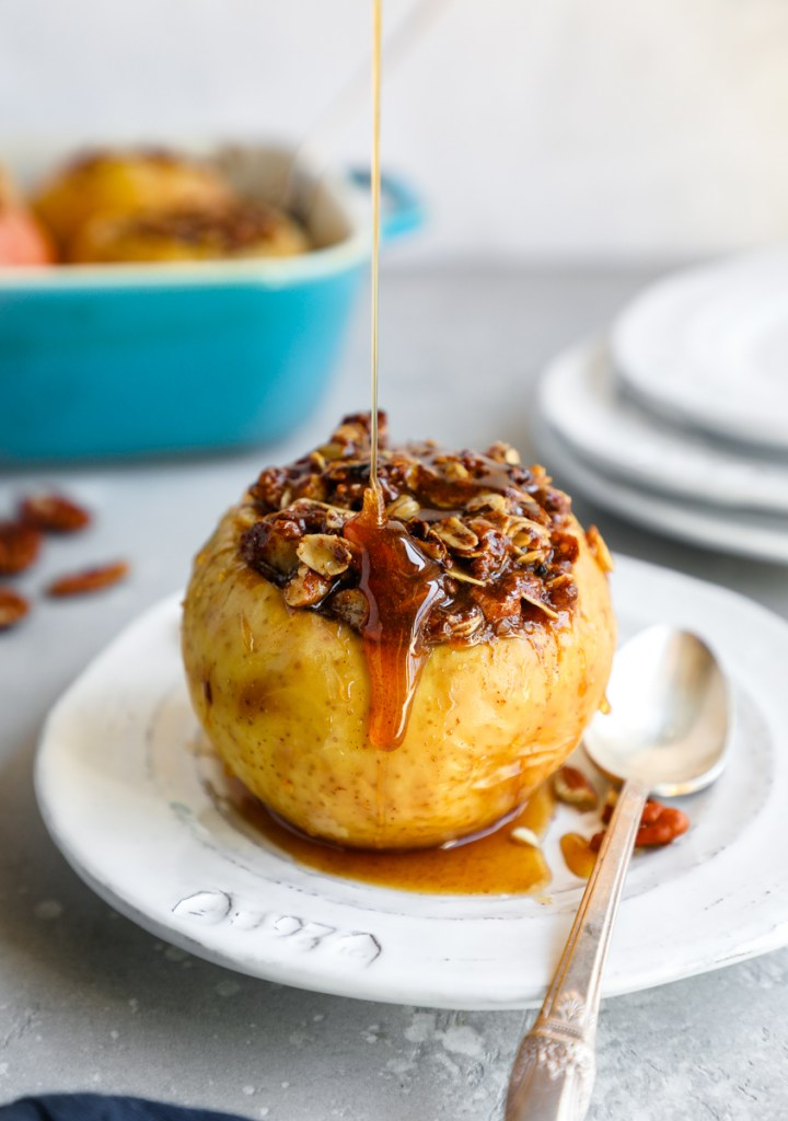 A baked apple stuffed with oat crumble and drizzled with honey sauce sitting on a white plate with a spoon