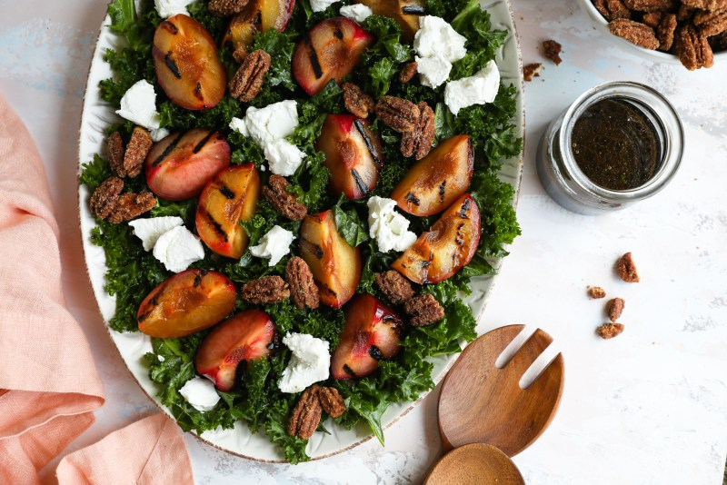 A grilled stone fruit kale salad surrounded by a jar of maple balsamic dressing, wooden salad tongs and a pink linen napkin