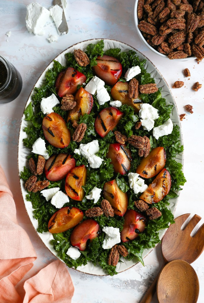 A large serving tray filled with a salad made with massaged kale, goat cheese, candied pecans and plumcots