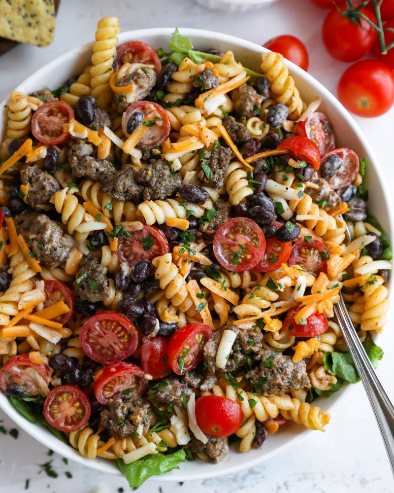 Taco pasta salad tossed in a creamy taco dressing with a silver spoon sticking out of the bowl