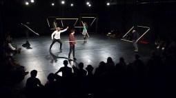 Le danseur et quelques spectateurs sont sur scène dans un décor très graphique fait de néons.