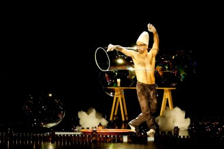 Sur scène, un décor original fait de flacons miniatures, où le danseur torse nu fabrique de grosses bulles de savons.