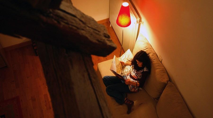Une jeune fille lit. Elle se trouve dans un habitat ancien qui a bénéficié de travaux de rénovation énergétique.