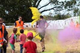 coureur sous une pluie de poudre colorée lancée par des enfants